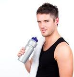 Athlethic junger Mann, der eine Sportflasche anhält Lizenzfreies Stockbild