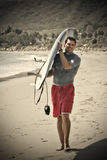 Athletic 30-something Male. An athletic, fit, 30-something Male carrying his surfboard to the beach. Warming filter, sepia toned photo Stock Image