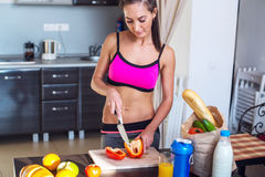 Athletic active sportive woman standing in kitchen royalty free stock image