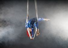 Athletic aerial circus artist with redhead in blue costume standing on one hand in the aerial silk stock photo