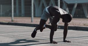Athletic African American man quickly bend legs in front plank in the street near the sports stadium. Fitness, health stock video