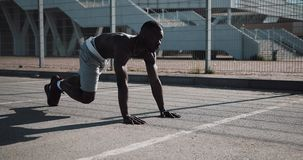 Athletic African American man quickly bend legs in front plank in the street near the sports stadium. Fitness, health stock video footage