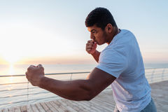 Athletic african sportsman boxing on pier in the morning Royalty Free Stock Photos