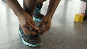Athletic Afro-American male tying shoelaces in the fitness club, sportswear. Stock footage stock video