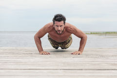 Athletic Army Doing Push Up Exercise at the Beach Stock Photo