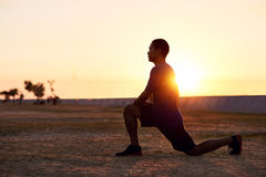 Athletic Asian man stretching his legs before a morning run Royalty Free Stock Photo