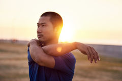 Athletic Asian man stretching his shoulders before a morning run. Focused athletic young Asian man stretching his arms before going for a solo run outside on a Royalty Free Stock Photos