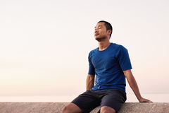 Athletic Asian man taking a breather during a morning run Stock Photos