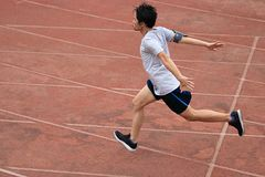 Athletic Asian runner sprinter crossing the finish line. Royalty Free Stock Images