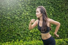 Athletic Asian woman running outdoors Stock Image