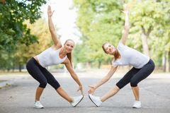 Athletic, attractive, fit girls working out together on a park background. Gymnastics concept. royalty free stock image