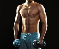 Athletic attractive man with dumbbells on the black Royalty Free Stock Photography