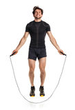 Athletic attractive man jumping on a rope on the white Royalty Free Stock Image