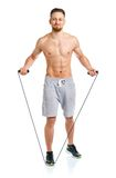 Athletic attractive man jumping on a rope on the white Royalty Free Stock Images