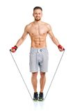 Athletic attractive man jumping on a rope on the white Stock Photos