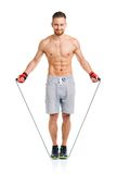 Athletic attractive man jumping on a rope on the white Royalty Free Stock Photo