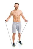 Athletic attractive man jumping on a rope on the white Stock Images