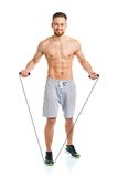 Athletic attractive man jumping on a rope on the white Stock Photography