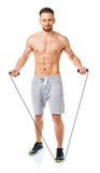 Athletic attractive man jumping on a rope on the white Royalty Free Stock Photos