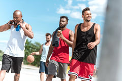 Athletic basketball players walking on court. Multiethnic group of athletic basketball players walking on court Stock Photography