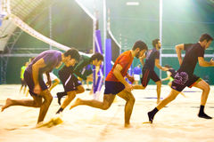 Athletic beach volleyball. Indoor. Athletic beach volleyball indoor. Group of boys running on the beach volleyball sand courts stock image