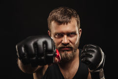 Athletic bearded boxer with gloves on a dark background Royalty Free Stock Photo