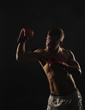Athletic bearded boxer with gloves on a dark background Stock Photo