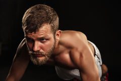 Athletic bearded boxer with gloves on a dark background Royalty Free Stock Images