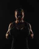 Athletic bearded boxer with gloves on a dark background Royalty Free Stock Image