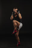 Athletic bearded boxer with gloves on a dark background Stock Image
