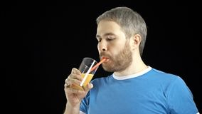 Athletic bearded gray haired man in blue t-shirt drinking orange juice with a straw. Black background. Athletic bearded gray haired man in blue t-shirt drinking Stock Photography