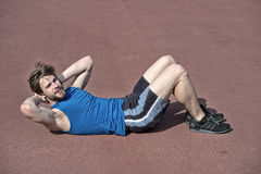 Athletic bearded man with muscular body doing exercises for abdominal. Athletic bearded man or handsome guy with muscular body doing exercises for abdominal on Royalty Free Stock Images