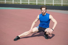 Athletic bearded man with muscular body stretching on running tr. Stretching. athletic bearded man or handsome guy with muscular body on running track sunny Royalty Free Stock Photos