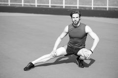 Athletic bearded man with muscular body stretching on running track. Stretching. athletic bearded man or handsome guy with muscular body on running track sunny Stock Images