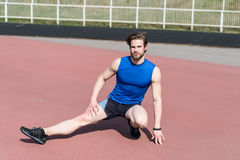 Athletic bearded man with muscular body stretching on running track. Stretching and workout. athletic bearded man or handsome guy with muscular body on running Royalty Free Stock Image