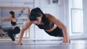 Athletic Beautiful Woman Doing Push-ups on the floor in Cross Fitness Gym. Sportswoman Exercising in the Gym. Crossfit. Training. Sporty girl trains triceps and stock video