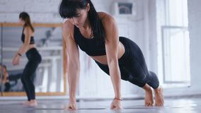 Athletic Beautiful Woman Doing Push-ups on the floor in Cross Fitness Gym. Sportswoman Exercising in the Gym. Crossfit. Athletic Beautiful Woman Doing Push-ups stock video