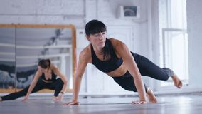 Athletic Beautiful Woman Doing Push-ups on the floor in Cross Fitness Gym. Sportswoman Exercising in the Gym. Crossfit. Athletic Beautiful Woman Doing Push-ups stock video footage