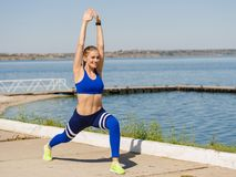 Cheerful, athletic girl on the outdoors training on a blurred background. Physical training concept. Copy space. Stock Image