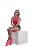 Athletic beauty woman with muscle body sit on cube Royalty Free Stock Photography