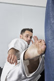Athletic black belt karate giving a forceful foot kick to a boxi Stock Photo