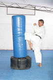 Athletic black belt karate giving a forceful knee kick during a Royalty Free Stock Images