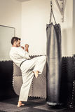 Athletic black belt karate giving a forceful knee kick during a Royalty Free Stock Image