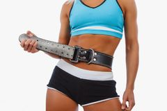 Woman`s stomach with weight lifting belt. Athletic blond female isolated on a white background royalty free stock images