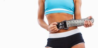 Woman`s stomach with weight lifting belt. Athletic blond female isolated on a white background royalty free stock image