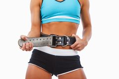 Woman`s stomach with weight lifting belt. Athletic blond female isolated on a white background stock images