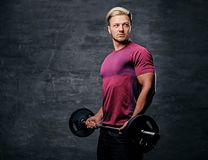 Blond male doing a biceps workout with a barbell. Athletic blond male doing a biceps workout with a barbell Stock Photo
