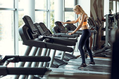 Athletic blond woman running on treadmill at gym. Royalty Free Stock Photography