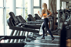 Athletic blond woman running on treadmill at gym. Stock Photos