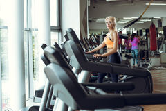 Athletic blond woman running on treadmill at gym. Stock Photo